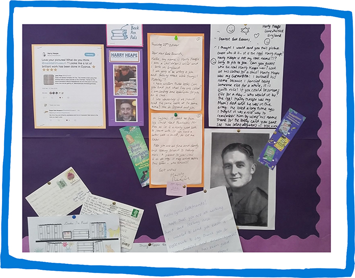 a school bulletin board displaying photos, school work and postcards from their Book Pen Pals experience with Harry Heape